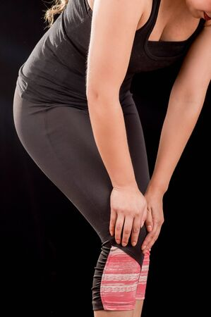 Close up of a beautiful young attractive sport woman holding injured knee suffering pain, in black background