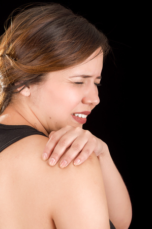 crick: Close up of a beautiful young woman suffer from shoulder pain in a black background