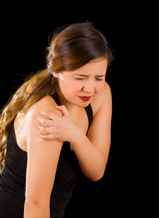 Beautiful young woman suffer from shoulder pain in a black background