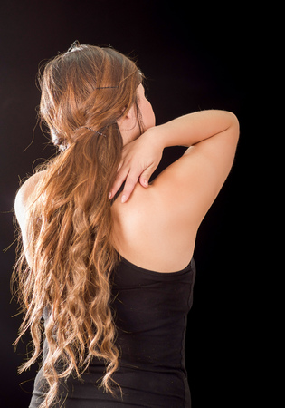 Beautiful young lady Suffer crick after workout in a black background