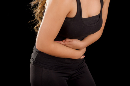 eyesclosed: Beautiful young woman with stomach ache or nausea in a black background