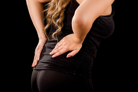 throbbing: Close up of a young beautiful sportwoman suffer cervical pain in her lower back, in black background