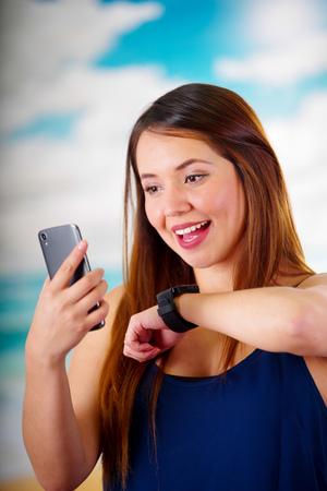 cardioid: Mujer de negocios que llevaba en su muñeca un reloj inteligente con control de voz y el uso de su teléfono celular, en un día soleado de fondo