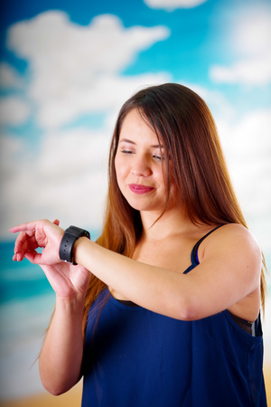 Business woman wearing in her wrist a smart watch with voice control in a sunny day background
