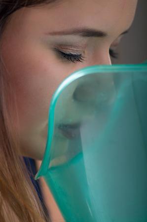 회색 배경에 기화기 nebulizer 기계와 흡입을하고 아름다운 여성의 닫습니다