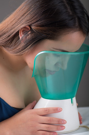 Young woman doing inhalation with a medical vaporizer nebulizer machine on black background Banco de Imagens