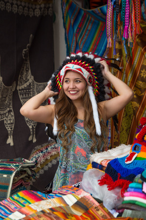 A beautiful young woman wearing Native American hat feather. with colorful fabrics background
