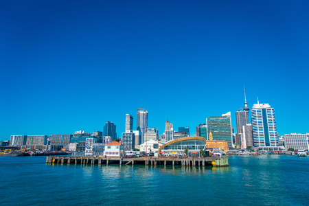 midday: AUCKLAND, NEW ZEALAND- MAY 12, 2017: Beautiful view of the largest and most populous urban area in Auckland with a wharf in front, in a sunny day