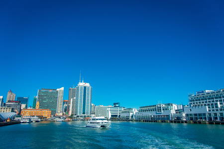 famous industries: AUCKLAND, NEW ZEALAND- MAY 12, 2017: Beautiful view of the largest and most populous urban area in Auckland with a ferry sailing, in a sunny day