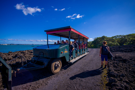 AUCKLAND, NEW ZEALAND- MAY 12, 2017: Unidentified people on a trip on a truck in a rocky road inside of the volcanic Rangitoto island, in a sunny day