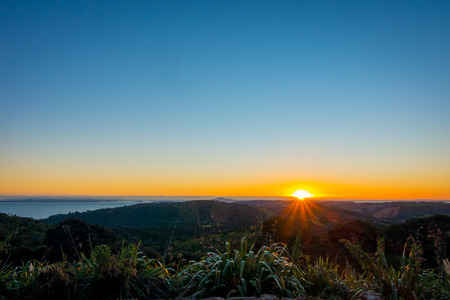 Beautiful sunset over the Hauraki Gulf, with trees and hills silhouetted in the foreground. Taken on the beach at Whakanewha Camp Ground on Waiheke Island, New Zealand Stock Photo