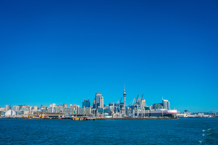 midday: AUCKLAND, NEW ZEALAND- MAY 12, 2017: Beautiful view of the largest and most populous urban area of Auckland, in the horizont with a blue sky in a sunny beautiful day