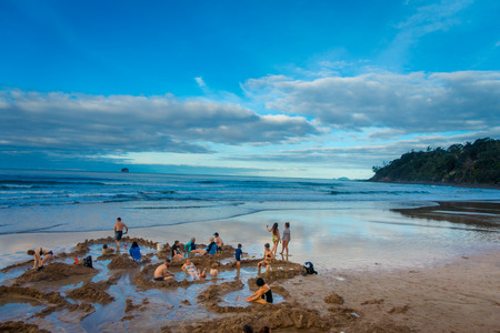 NORTH ISLAND, NEW ZEALAND- MAY 16, 2017: Tourists digging their own hot springs in Hot Water Beach, Coromandel. 130,000 annual visitors make it one of most popular attractions in Waikato region, in New Zealand