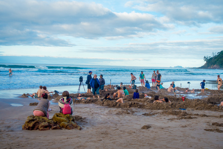 dug: NORTH ISLAND, NEW ZEALAND- MAY 16, 2017: Tourists digging their own hot springs in Hot Water Beach, Coromandel. 130,000 annual visitors make it one of most popular attractions in Waikato region, in New Zealand