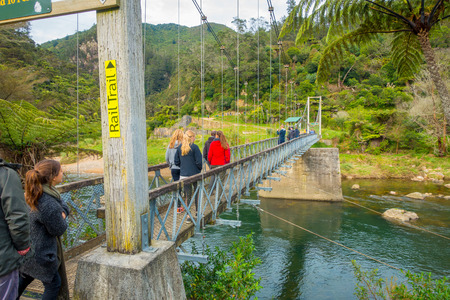 NORTH ISLAND, NEW ZEALAND- MAY 16, 2017: Unidentified people walking through the Bridge to cross the river to visit karangahake rail tunnel via gorge, in North Island in New Zealand