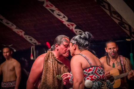 NORTH ISLAND, NEW ZEALAND- MAY 17, 2017: Tamaki Maori couple dancing with traditionally tatooed face in traditional dress at Maori Culture, Tamaki Cultural Village, in New Zealand Editorial