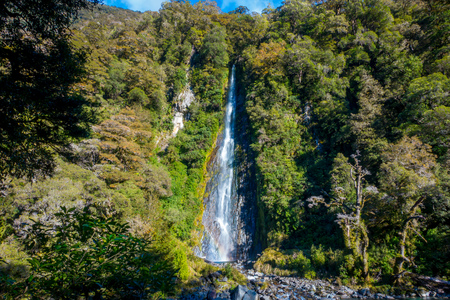 Billy Falls with the Glacial Blue river water flowing over rocks. Haast Pass, South Island, New Zealand Stock Photo