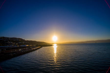 provide: SOUTH ISLAND, NEW ZEALAND- MAY 25, 2017: Beautiful sunset in the horizont, looking from Ferry that provide daily connection between North and South islands with a beautiful blue sky located in New Zealand