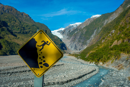 franz: SOUTH ISLAND, NEW ZEALAND- MAY 25, 2017: A yellow sign of wreck danger in a beautiful landscape of Franz Josef Glacier National Park, in New Zealand