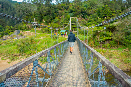 NORTH ISLAND, NEW ZEALAND- MAY 16, 2017: Unidentified man walking through the Bridge to cross the river to visit karangahake rail tunnel via gorge, in North Island in New Zealand Editorial