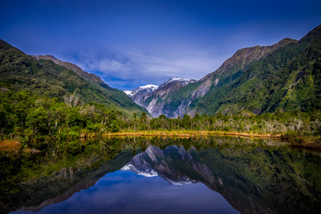Small pond peters pond with reflection of mountain glacier Franz Josef Glacier in New Zealand