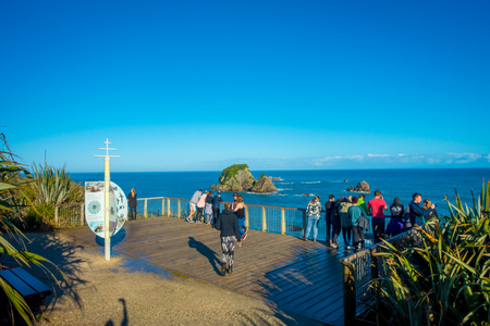 SOUTH ISLAND, NEW ZEALAND- MAY 23, 2017: Unidentified people looking at wall Island near Cape Foulwind, View from the Cape Foulwind walkway at the Seal Colony, Tauranga Bay. New Zealand Editorial