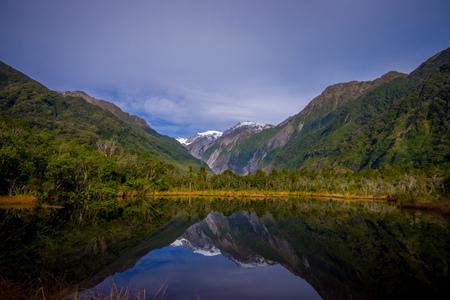 fox glacier: Small pond peters pond with reflection of mountain glacier Franz Josef Glacier in New Zealand
