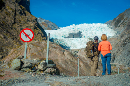 molly: Unidentified couple enoying the view of the Franz Josef Glacier and valley floor, Westland, South Island, Franz Josef Glacier National Park, in New Zealand