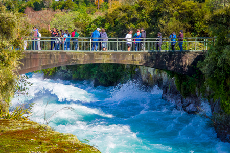 A crown of people over the bridge enjoying the view of the powerful Huka Falls on the Waikato River near Taupo North Island New Zealand