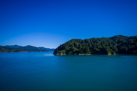 Beautiful landscape of mountain with gorgeous blue sky in a sunny day seen from ferry from north island to south island, in New Zealand