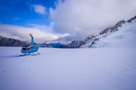 SOUTH ISLAND, NEW ZEALAND- MAY 24, 2017: Helicopter and pilot waiting over the snow for hunters in South Westlands Southern Alps, New Zealand Editorial
