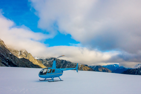 SOUTH ISLAND, NEW ZEALAND- MAY 24, 2017: Close up of blue helicopter waiting over the snow for hunters in South Westlands Southern Alps, New Zealand Editorial