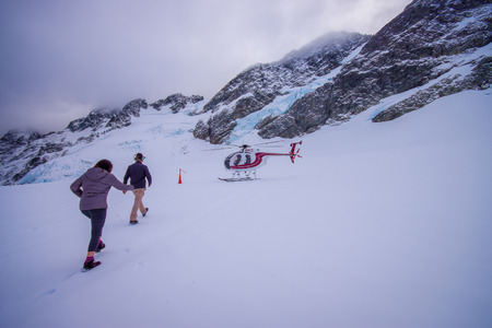 SOUTH ISLAND, NEW ZEALAND- MAY 24, 2017: Unidentified people walking to the helicopter, waiting over the snow for hunters in South Westlands Southern Alps, New Zealand