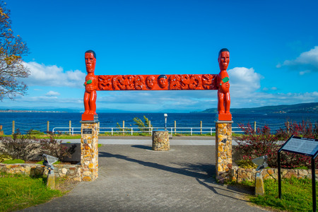 NORTH ISLAND, NEW ZEALAND- MAY 18, 2017: Beautiful red sculpture donated by Lucy Reid, view of wharf, and lovely view of Lake Taupo with mountains an city in the background at spring, North Island of New Zealand with beautiful blue sky Editorial