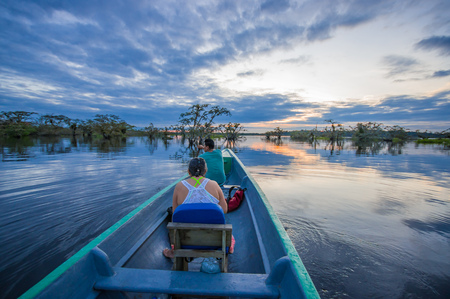 People enjoying the sunset from the river in Cuyabeno National Park, Ecuador Stock Photo
