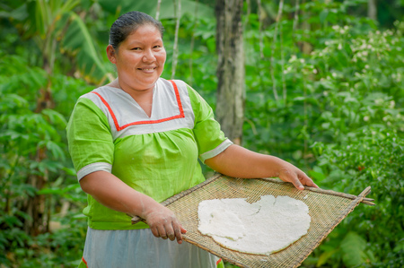 LAGO AGRIO, ECUADOR - NOVEMBER, 17 2016: Woman demonstrates cooking yucca tortillas in an outdoor kitchen in a Siona village in the Cuyabeno Wildlife Reserve, Ecuador Sajtókép
