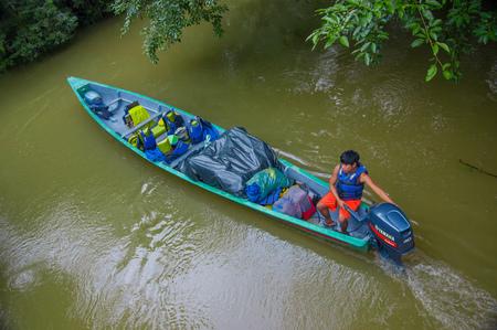 CUYABENO, ECUADOR - NOVEMBER 16, 2016: Unidentified man travelling by boat into the depth of Amazon Jungle in Cuyabeno National Park, Ecuador