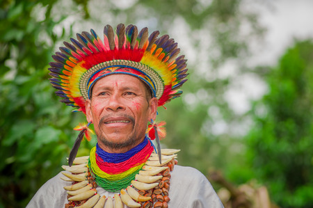 LAGO AGRIO, ECUADOR - NOVEMBER 17, 2016: Close up of a Siona shaman in traditional dress with a feather hat in an indigenous village in the Cuyabeno Wildlife Reserve