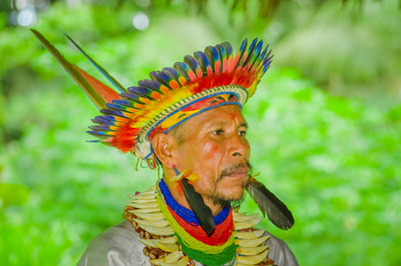 LAGO AGRIO, ECUADOR - NOVEMBER 17, 2016: Portrait of a Siona shaman in traditional dress with a feather hat in an indigenous village in the Cuyabeno Wildlife Reserve