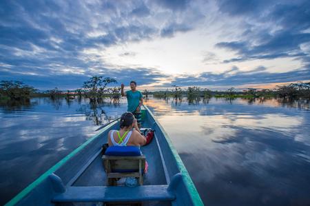 CUYABENO, ECUADOR - NOVEMBER 16, 2016: Unidentified people enjoying the sunset from the river in Cuyabeno National Park, Ecuador