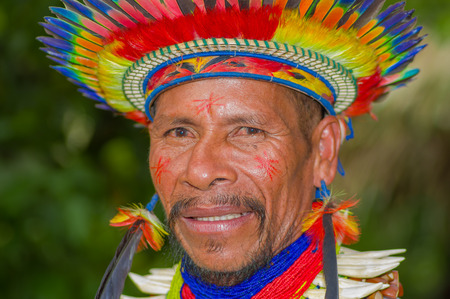 ecstasy: LAGO AGRIO, ECUADOR - NOVEMBER 17, 2016: Portrait of a Siona shaman in traditional dress with a feather hat in an indigenous village in the Cuyabeno Wildlife Reserve