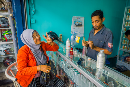 essences: BALI, INDONESIA - MARCH 08, 2017: Unidentified man using syringes and pipettes mixing essences to prepare perfumes, while a woman is buying a perfume in the perfume store in Denpasar Indonesia