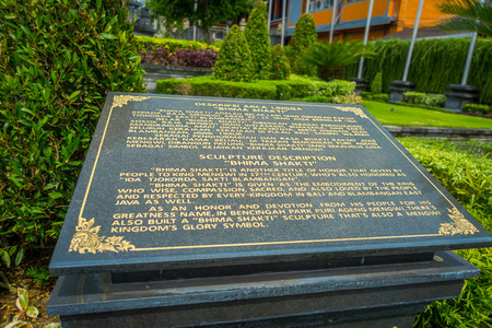 Informative sign on a black cement Stone statue of Vishnu in Gunung Kawi, Bali, Indonesia