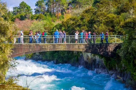 SOUTH ISLAND, NEW ZEALAND- MAY 23, 2017: A crown of people over the bridge enjoying the view of the powerful Huka Falls on the Waikato River near Taupo North Island New Zealand Editorial