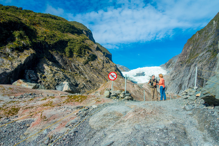 molly: SOUTH ISLAND, NEW ZEALAND- MAY 23, 2017: Unidentified couple enoying the view of the Franz Josef Glacier and valley floor, Westland, South Island, Franz Josef Glacier National Park, in New Zealand Editorial