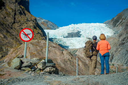 SOUTH ISLAND, NEW ZEALAND- MAY 23, 2017: Unidentified couple enoying the view of the Franz Josef Glacier and valley floor, Westland, South Island, Franz Josef Glacier National Park, in New Zealand Editorial