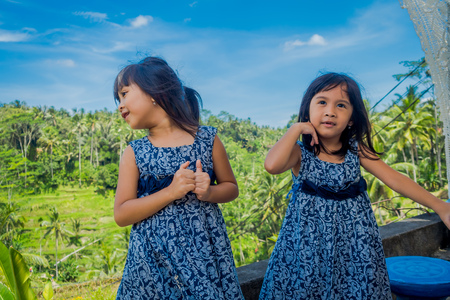 BALI, INDONESIA - APRIL 05, 2017: Two beautiful girls wearing a dress in a sunny day, in Ubud Indonesia