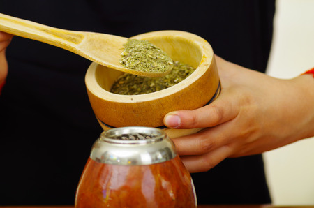 Woman holding bowl with green herbs preparing traditional cup of popular drink called mate, typical metal straw sticking up