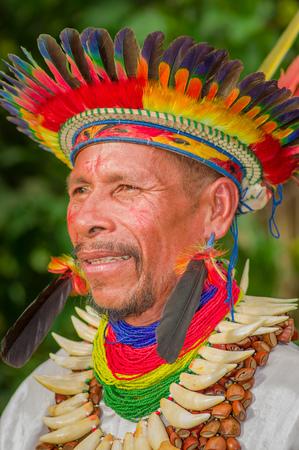 éxtasis: LAGO AGRIO, ECUADOR - 17 DE NOVIEMBRE DE 2016: Retrato de un chamán Siona en traje tradicional con un sombrero de plumas en un pueblo indígena en la Reserva de Fauna Cuyabeno