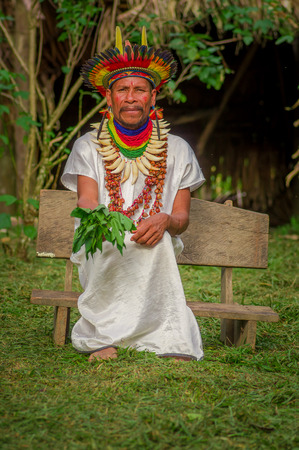 illustrative editorial: LAGO AGRIO, ECUADOR - NOVEMBER 17, 2016: Siona shaman in traditional dress with a feather hat in an indigenous village in the Cuyabeno Wildlife Reserve Editorial
